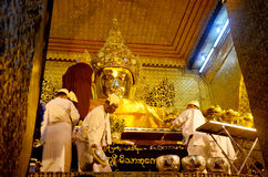 Monks wash the face and brush the teeth of the Buddha image at Maha Myat Muni Stock Photos