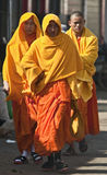 Monks in Yellow. Three monks walk through the busy market streets wearing their traditional yellow and orange robes Royalty Free Stock Images