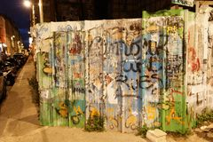 Monmartre grafitti on a wall. Paris - August 2, 2017: A graffiti covered wall in Monmartre at night royalty free stock images