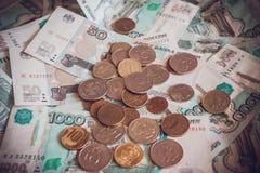 Monnaie fiduciaire et pièces de monnaie sur la table Photographie stock libre de droits