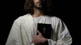 Monnik die in witte robe heilige bijbel houden tegen donkere achtergrond, Christendom stock footage
