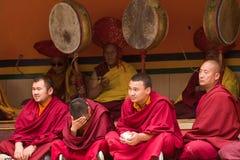 Monniken als aandachtige toeschouwers en rituele festivalslagwerkers lama stock fotografie