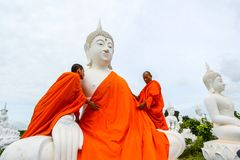 Monniken die één van het Witte Beeld van Boedha met robes kleden stock foto's