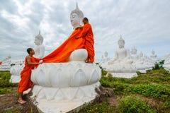 Monniken die één van het Witte Beeld van Boedha met robes kleden stock afbeelding