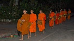 Monniken die aalmoes verzamelen bij dageraad in Luang Prabang op November 2013 Royalty-vrije Stock Afbeeldingen