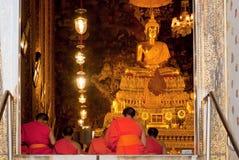 Monniken die bij het gouden standbeeld van Boedha in historisch klooster bidden Royalty-vrije Stock Afbeelding