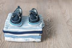 Mono azul y blanco doblado con los zapatos en él fondo de madera gris pañal para el muchacho recién nacido Pila de ropa infantil  Imágenes de archivo libres de regalías