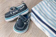 Mono azul y blanco doblado con los zapatos en él fondo de madera gris pañal para el muchacho recién nacido Pila de ropa infantil  Imagen de archivo libre de regalías