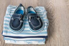 Mono azul y blanco doblado con los zapatos en él fondo de madera gris pañal para el muchacho recién nacido Pila de ropa infantil  Foto de archivo libre de regalías