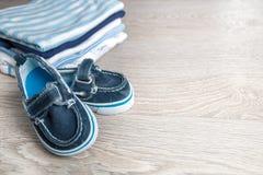 Mono azul y blanco doblado con los zapatos en él fondo de madera gris pañal para el muchacho recién nacido Pila de ropa infantil  Fotografía de archivo libre de regalías