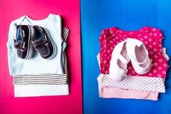 Mono azul y rosado doblado con los zapatos del barco en él en fondo rosado y azul minimalistic pañal para el muchacho y la muchac Fotografía de archivo