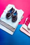 Mono azul y rosado doblado con los zapatos del barco en él en fondo rosado y azul minimalistic pañal para el muchacho y la muchac Imagenes de archivo
