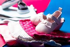 Mono azul y rosado doblado con los zapatos del barco en él en fondo rosado y azul minimalistic pañal para el muchacho y la muchac Fotos de archivo libres de regalías