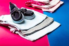 Mono azul y rosado doblado con los zapatos del barco en él en fondo rosado y azul minimalistic pañal para el muchacho y la muchac Imágenes de archivo libres de regalías
