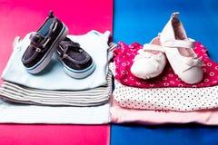 Mono azul y rosado doblado con los zapatos del barco en él en fondo rosado y azul minimalistic pañal para el muchacho y la muchac Fotos de archivo