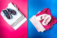 Mono azul y rosado doblado con los zapatos del barco en él en fondo rosado y azul minimalistic pañal para el muchacho y la muchac Fotografía de archivo libre de regalías
