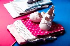 Mono azul y rosado doblado con los zapatos del barco en él en fondo rosado y azul minimalistic pañal para el muchacho y la muchac Imagen de archivo libre de regalías