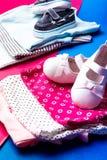 Mono azul y rosado doblado con los zapatos del barco en él en fondo rosado y azul minimalistic pañal para el muchacho y la muchac Foto de archivo libre de regalías