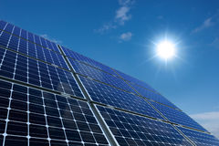 Mono-crystalline solar panels against a sunny sky Stock Photo