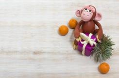 Mono de la plastilina con Años Nuevos regalo y mandarinas Foto de archivo
