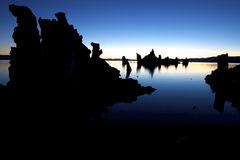 Mono Lake silhouettes. Sunrise with tufa formations in silhouettes against blue sky and water of Mono Lake, USA Stock Photography