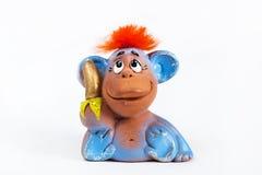 Mono rojo del pelo con el plátano en el fondo blanco Foto de archivo libre de regalías
