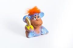 Mono rojo del pelo con el plátano en el fondo blanco Imágenes de archivo libres de regalías