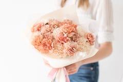 Monoboeket van kruidnagels Gevoelig boeket van gemengde bloemen in de handen van de vrouw het werk van de bloemist bij een bloemw royalty-vrije stock foto