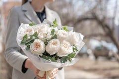 Monoboeket van tuinrozen Gevoelig boeket van gemengde bloemen in de handen van de vrouw het werk van de bloemist bij een bloem royalty-vrije stock afbeelding