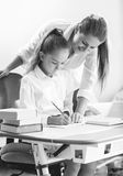 Monochorme portrait of mother doing homework with daughter Stock Photos