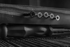 Monochroe驱散了螺丝被拧紧入木板条和螺丝刀 免版税库存照片