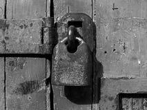 monochrom zamknięty w górę starej ośniedziałej zamkniętej zasuwki na zakłopotanym drewnianym deski drzwi i kłódki zdjęcia stock