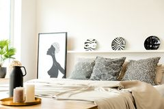 Monochromatic bedroom interior with poster. Patterned plates on shelf above bed in monochromatic bedroom interior with poster stock images