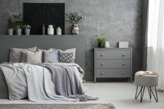 Monochromatic grå sovruminre med en stor säng med kast a fotografering för bildbyråer