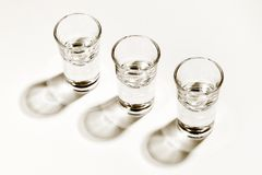 Monochromatic image of three empty shot glasses, harsh side lighted with hard shadows. High angle view. Monochrome image of three empty shot glasses, harsh side stock images