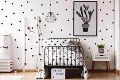Monochromatic kids room with plant. White ladder against white wallpaper with black dots in monochromatic kids room with plant stock image