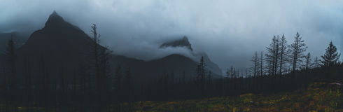 Monochromatic panorama of mountain peaks covered in clouds. Royalty Free Stock Photos