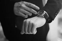 Monochromatyczny obrazek przyglądający up na jego zegarkach szef Zdjęcie Stock