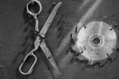 Monochromatyczny tło z starymi nożycami i kurendą zobaczył ostrze obrazy stock
