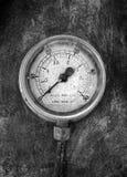 Monochrome изображение круглого промышленного манометра с номерами вокруг шкалы установило на поверхности металла стоковая фотография