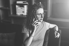 monochrome изображение Молодой битник бизнес-леди в стеклах сидит на софе в офисе и говорит на сотовом телефоне Стоковая Фотография