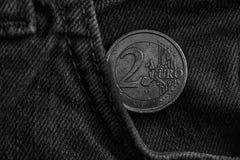 Monochrome монетка евро с деноминацией евро 2 в карманн старых винтажных голубых джинсов джинсовой ткани Стоковая Фотография