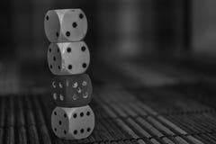 Monochrome стог пластмассы 3 dices и кости одного красного цвета на предпосылке деревянной доски 6 кубов сторон с черными точками Стоковое Изображение