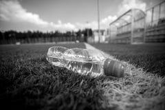 Monochrome съемка бутылки воды лежа на футбольном поле Стоковая Фотография RF