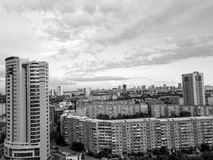 Monochrome aerial view of one skyscraper and old long building. In the city with sky and clouds on horizont. Black and white russian streets, Novosibirsk Stock Photography