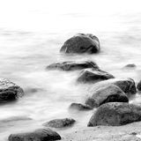 Black and white impression of the evening sea shore with water and stones on a beach. Monochrome artistic impression of the evening shore sea water and stones on Royalty Free Stock Image