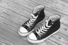 Monochrome black and white grunge wooden background with vintage canvas sneakers Stock Image
