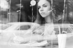 Monochrome black and white Portrait of an attractive young journalist girl with pen and notepad in a cafe behind the royalty free stock image