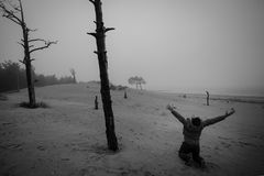 Monochrome of Depressed Man n Has on a Lap Raised Hands Up Against the Background of Dead Trees. Depressed Man n Has on a Lap Raised Hands Up Against the Royalty Free Stock Photos