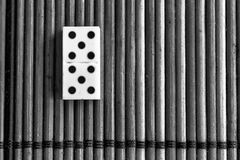 Monochrome Domino piece on the bamboo brown wooden table background. Domino set - five - 5 dots.  royalty free stock image